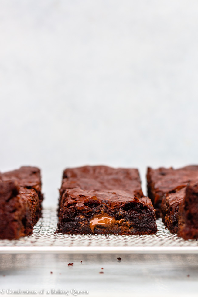 thick and chewy brownies on a silver wire rack on top of a white marble background