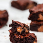 thick and chewy brownies baked and stacked on top of each other broken apart showing melted chocolate on a white marble background