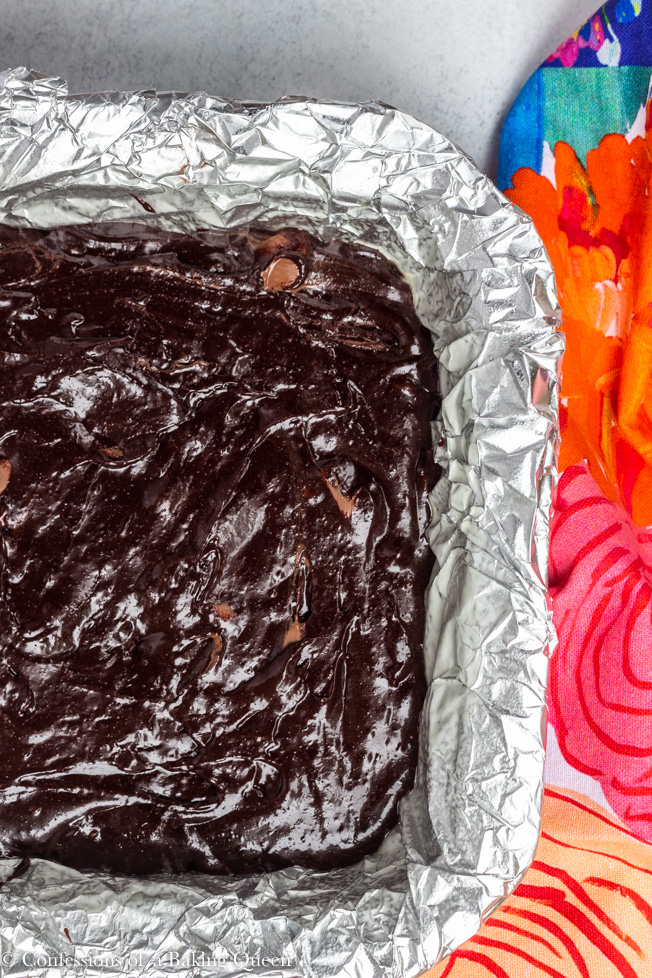 thick and chewy brownie recipe poured into prepared foil lined pan ready to bake on a light white/ grey surface with a colorful multi colored linen