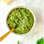easy walnut pesto recipe served in a small bowl with a gold spoon on a white marble surface with a block of parmesan cheese and basil leaves