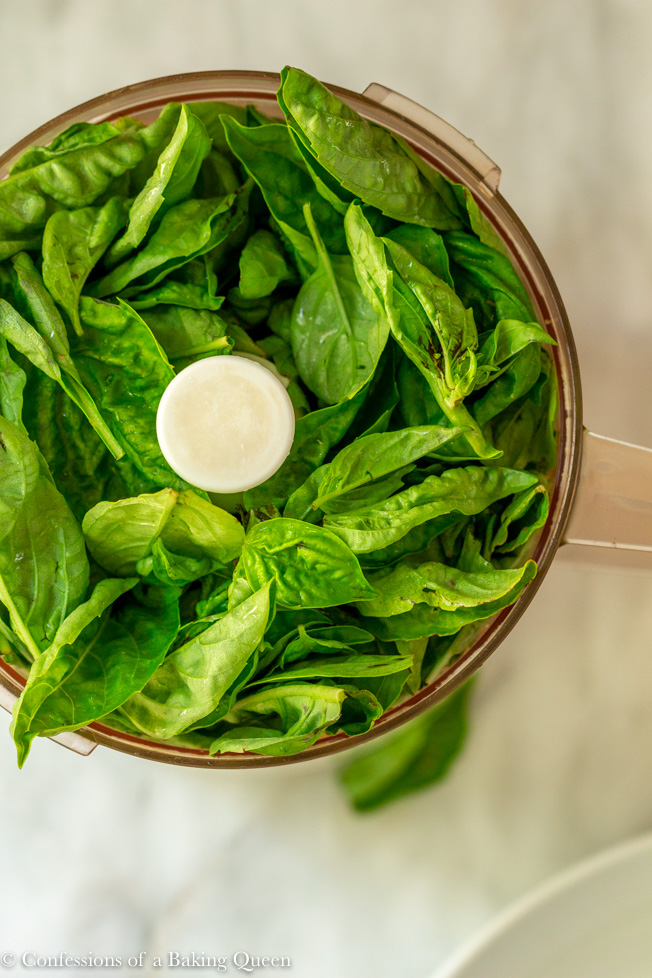 fresh basil leaves in food processor on a white surface