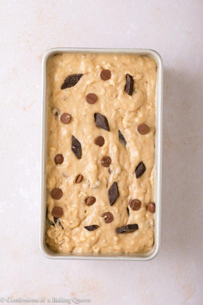 chocolate chunk banana bread in a loaf pan before baking on a light surface