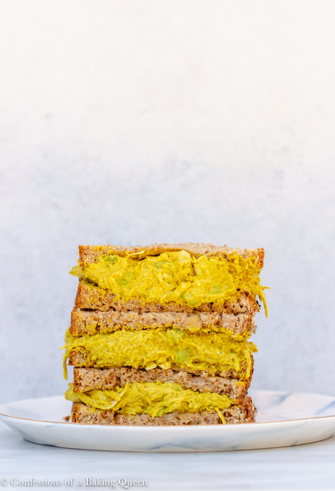 curried chicken salad recipe served in a sandwich, three halves of sandwiches stacked on top of each other on a white and blue plate