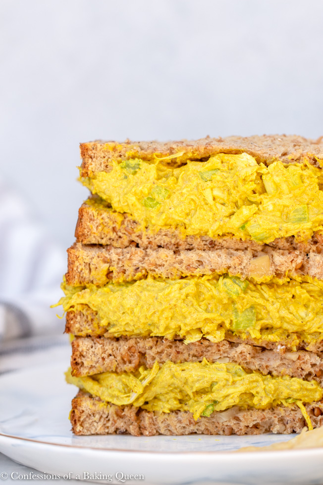 close up of curried chicken salad recipe served in a sandwich, three halves of sandwiches stacked on top of each other on a white and blue plate