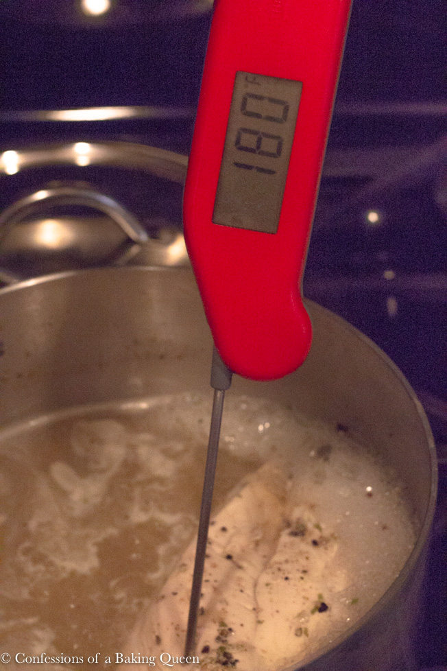 instant read thermometer inside chicken in a boiling pot on dark stove