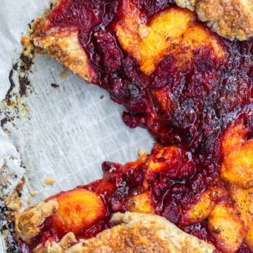 Peach Raspberry Galette Recipe with a slice cut out on parchment paper on a wire rack