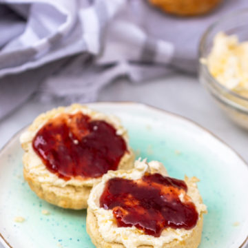 fresh baked sones with clotted cream and jam on a teal plate on a white background with a grey tea towel