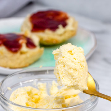 clotted cream in a clear bowl with a gold spoon holding a scoop with scones in the background on a white surface