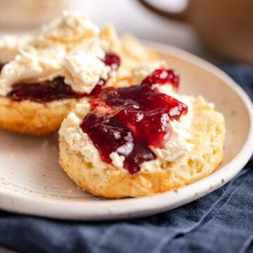 scones with clotted cream and jam on a white plate on a blue napkin and a cup of tea in the background