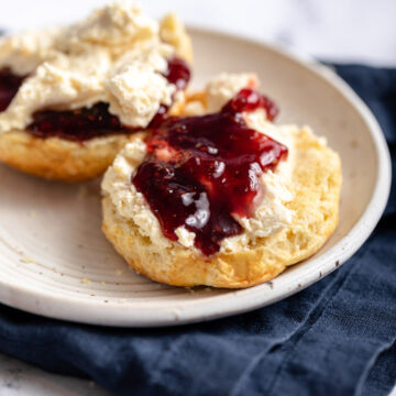 scones with clotted cream and jam on a white plate on a blue napkin