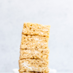 brown butter rice krispies stacked high on a marble counter top with mini marshmallows on a white marble surface