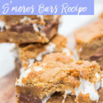 cookie butter smores bar with a bite taken out on a white and wood board