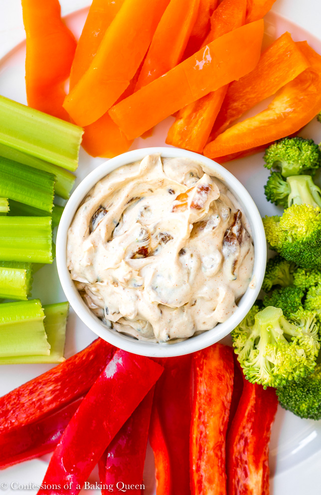 french onion dip serve in a white bowl with fresh cut veggies on a large white plate