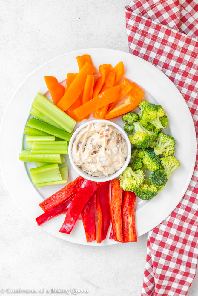 french onion dip and fresh cut vegetables served on a large white plate with a red and white napkin beneath it