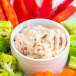 french onion dip in the center of the plate with fresh cut peppers, broccoli and celery
