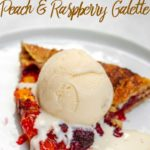 peach raspberry galette recipe baked and sliced served with a scoop of vanilla ice cream on a white plate on a white surface
