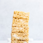 brown butter rice krispies stacked high on a marble counter top with mini marshmallows