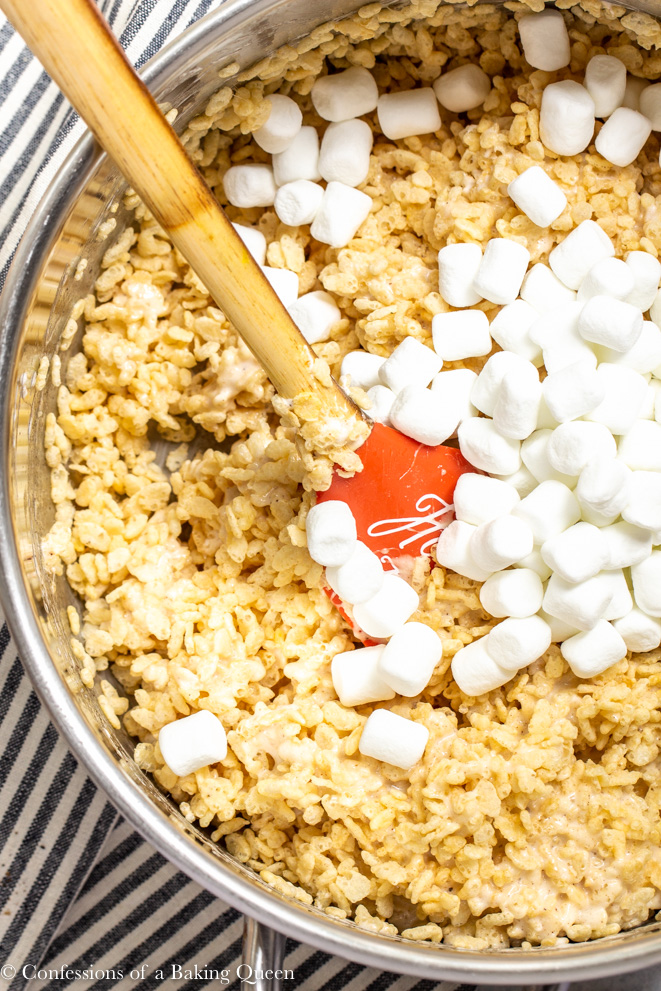 extra marshmallows being added to brown butter rice krispies on a white surface with a stripped linen