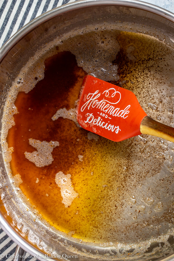 butter being browned in a a large pot with an orange spatula on a white surface with a stripped linen