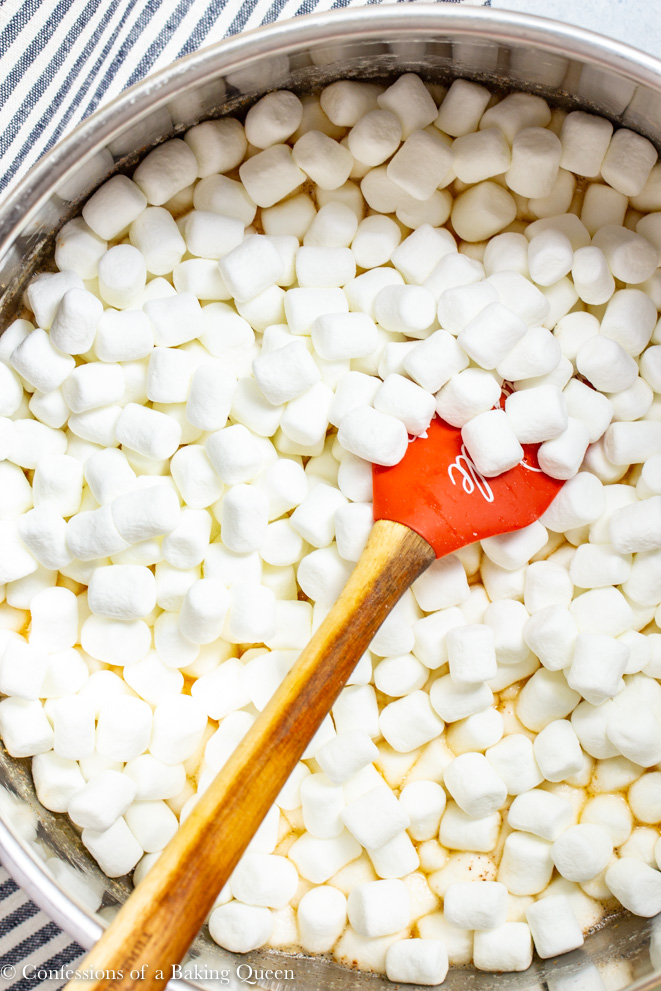 marshmallows added to a large pot with a orange spatula on a white surface with a stripped linen