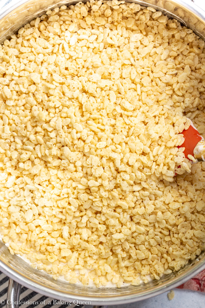 rice krispies being added to marshmallows for brown butter rice krispies recipe on a white surface with a stripped linen