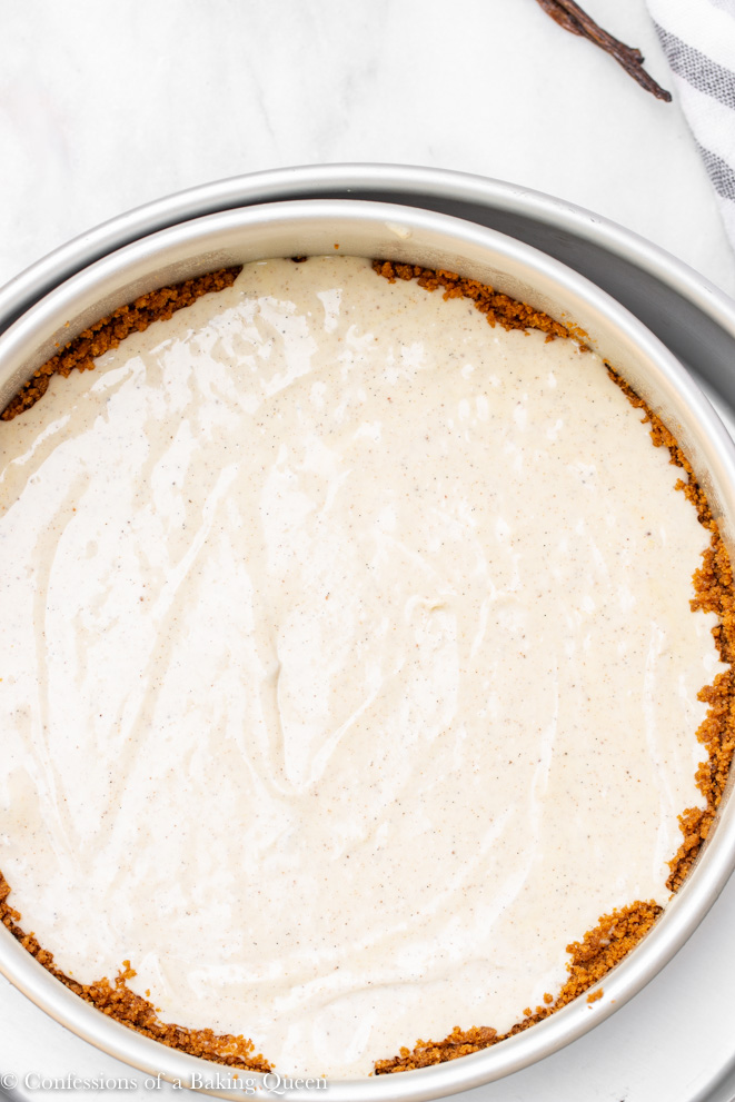 chai cheesecake in a round silver pan ready to be baked