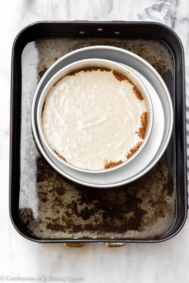 chai cheesecake in a water bath in roasting pan on a white surface