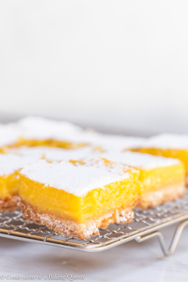 lemon bars dusted with powdered sugar cooling on a wire rack