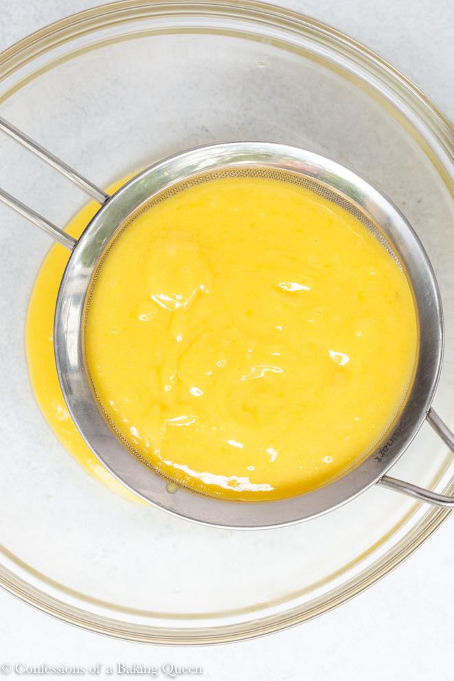 lemon filling strained through a mesh strainer for a how to make lemon bars recipe
