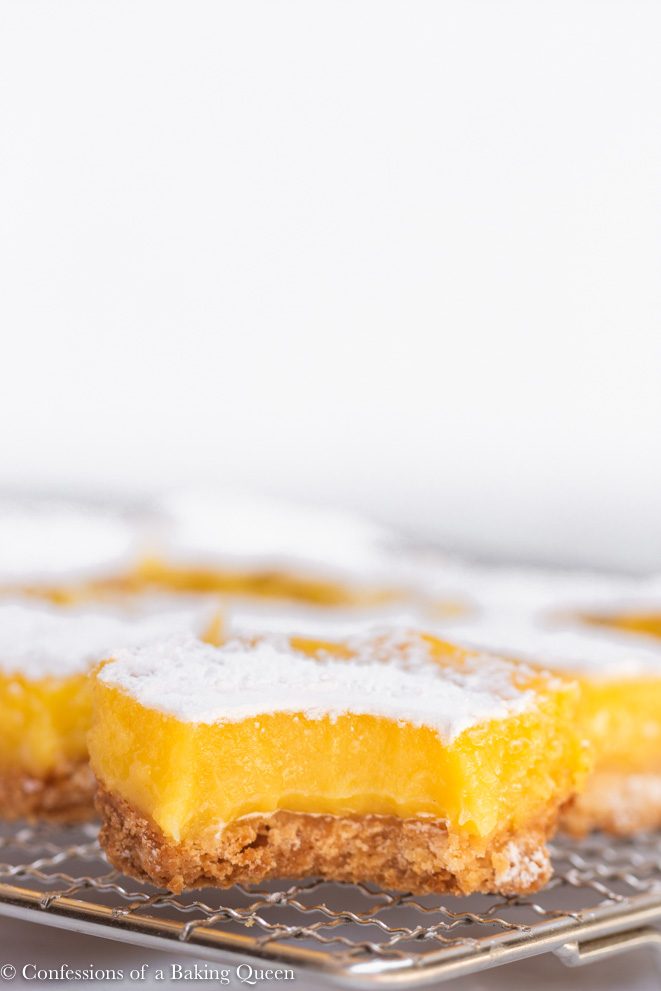 head on shot of a lemon bar with a bite taken out sitting on a wire rack with more lemon bars behind