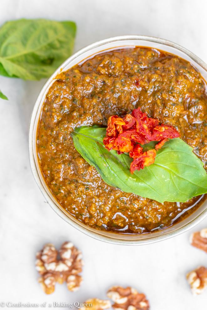 sun dried tomato basil recipe served in a small bowl on marble top with walnuts and basil leaves