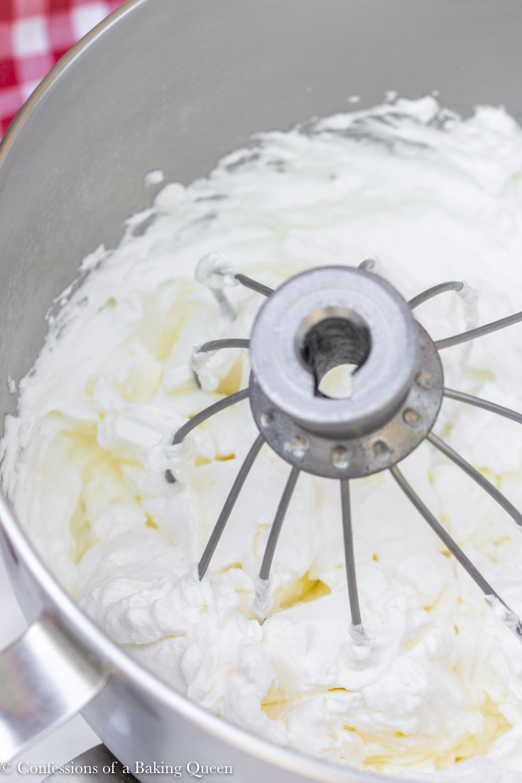 whipped cream in a metal bowl with a whisk attachment in it