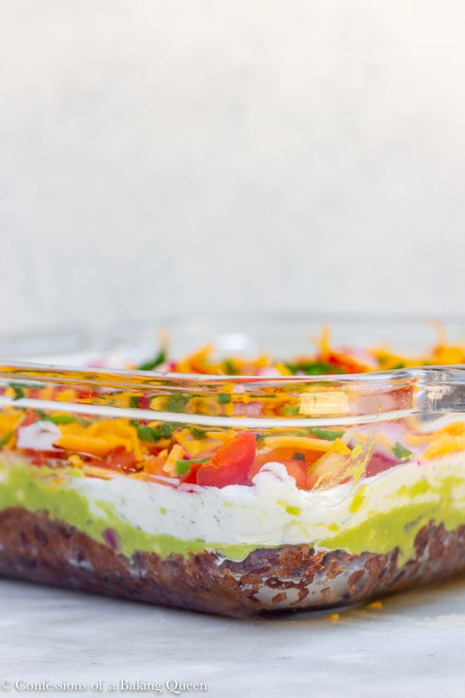 head on shot of seven layer dip recipe on a white counter