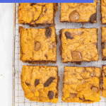 chocolate chunk blondies cut into squares cooling on a wire rack on a white marble surface