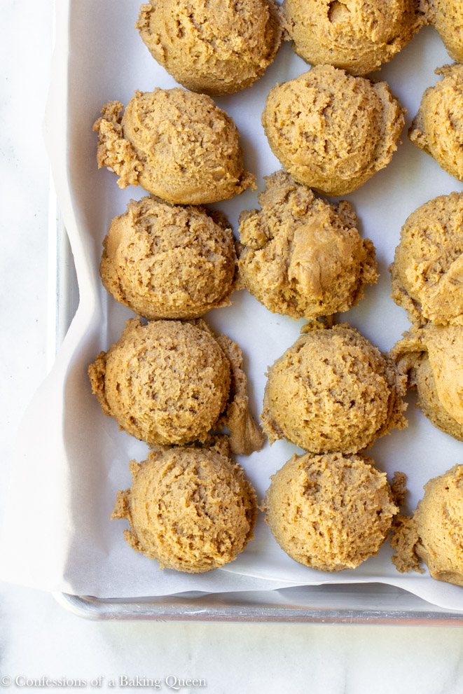 guinness gingerbread cookie dough scooped into balls on a parchment lined metal baking pan