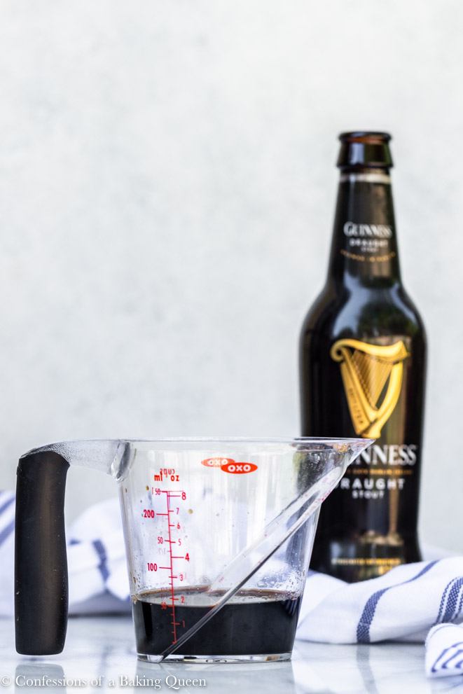 guinness reduced in a clear measuring cup with a bottle of guinness in the background