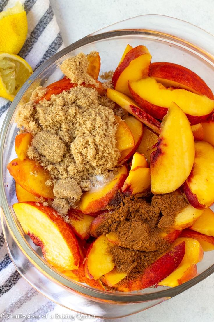 sliced peaches, cinnamon and brown sugar in a large clear bowl for a peach crumble recipe