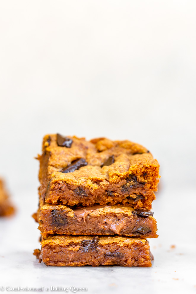 a stack of chewy chocolate chunk pumpkin blondies on a white marble surface