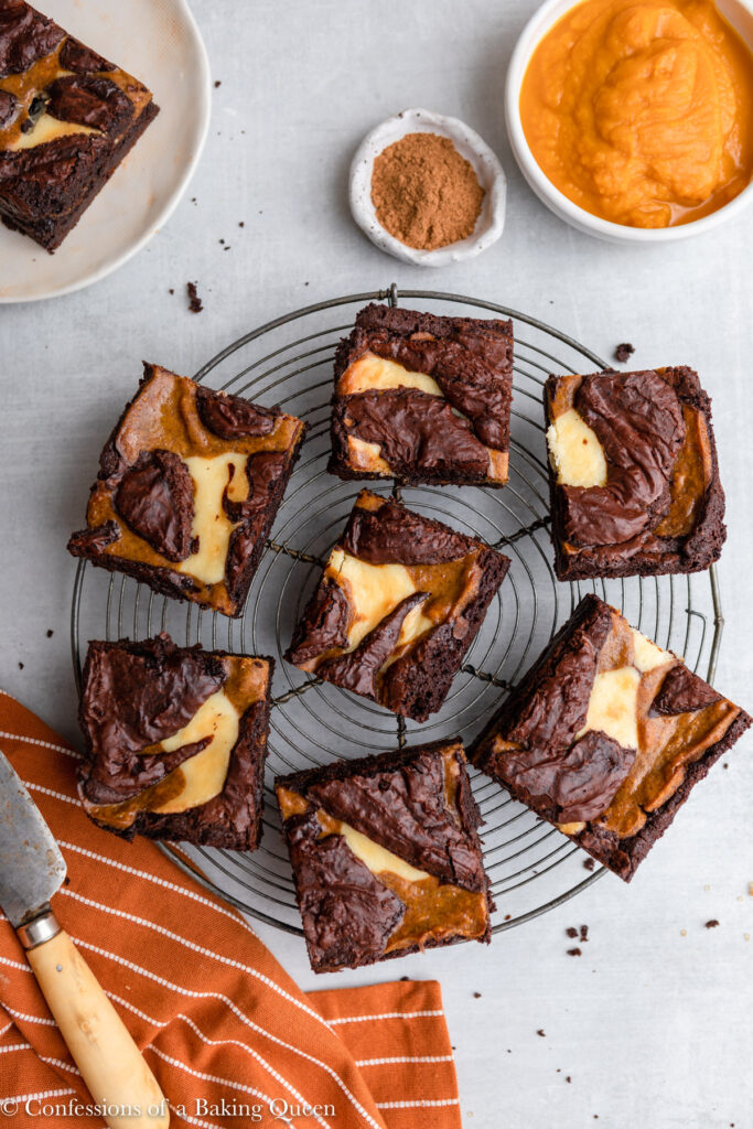 pumpkin cheesecake brownies ona wire rack on a grey surface with a orange linen, knife, bowl of pumpkin puree, and plate of brownies