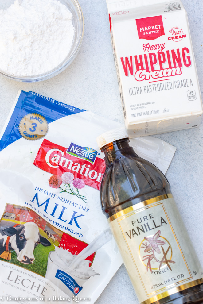 dry milk powder, powdered sugar, vanilla and heavy whipping cream laid out to be used for a stabilized whipped cream recipe