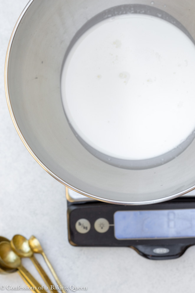 heavy cream in a large metal bowl on a digital kitchen scale
