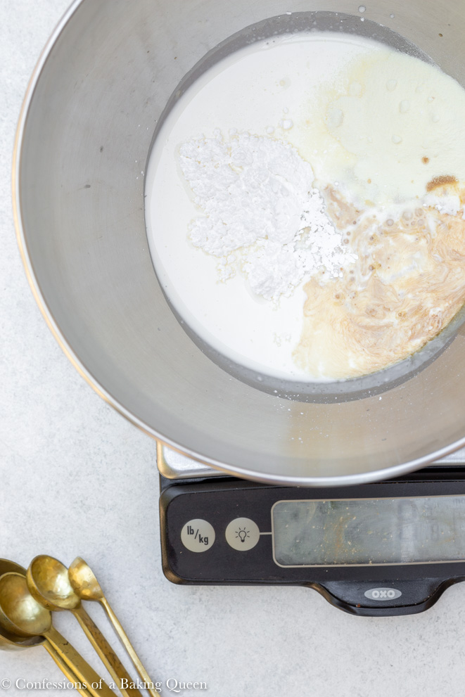 ingredients in a large metal bowl sitting on top of a digital scale