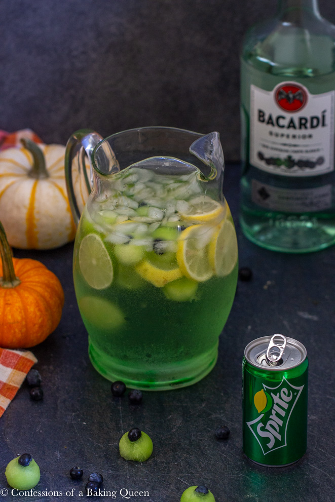 Eyeball Rum Punch pitcher, can of sprite, and a bottle of Bacardi rum on a dark grey surface with two pumpkins on the side