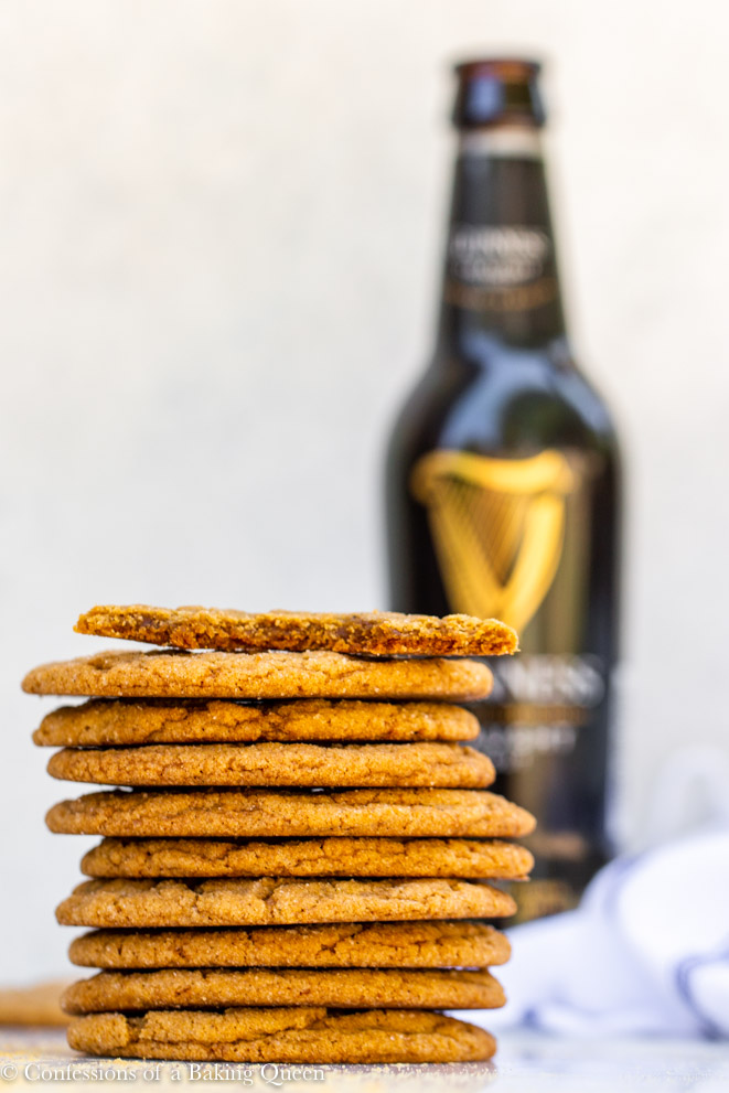 half eaten cookie on a stack of full cookies with a bottle of guinness in the backgground