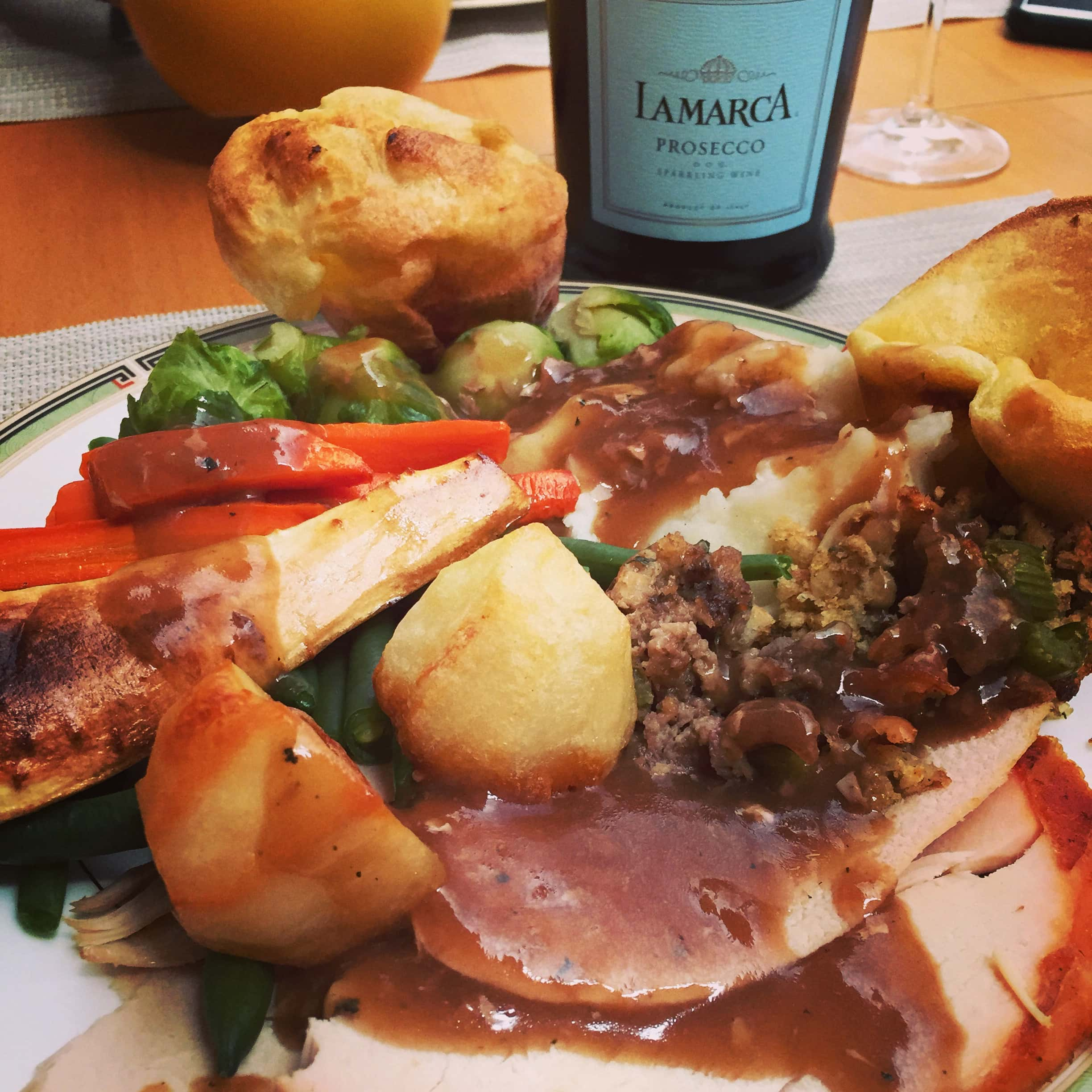 roast dinner on a plate with prosecco in the background