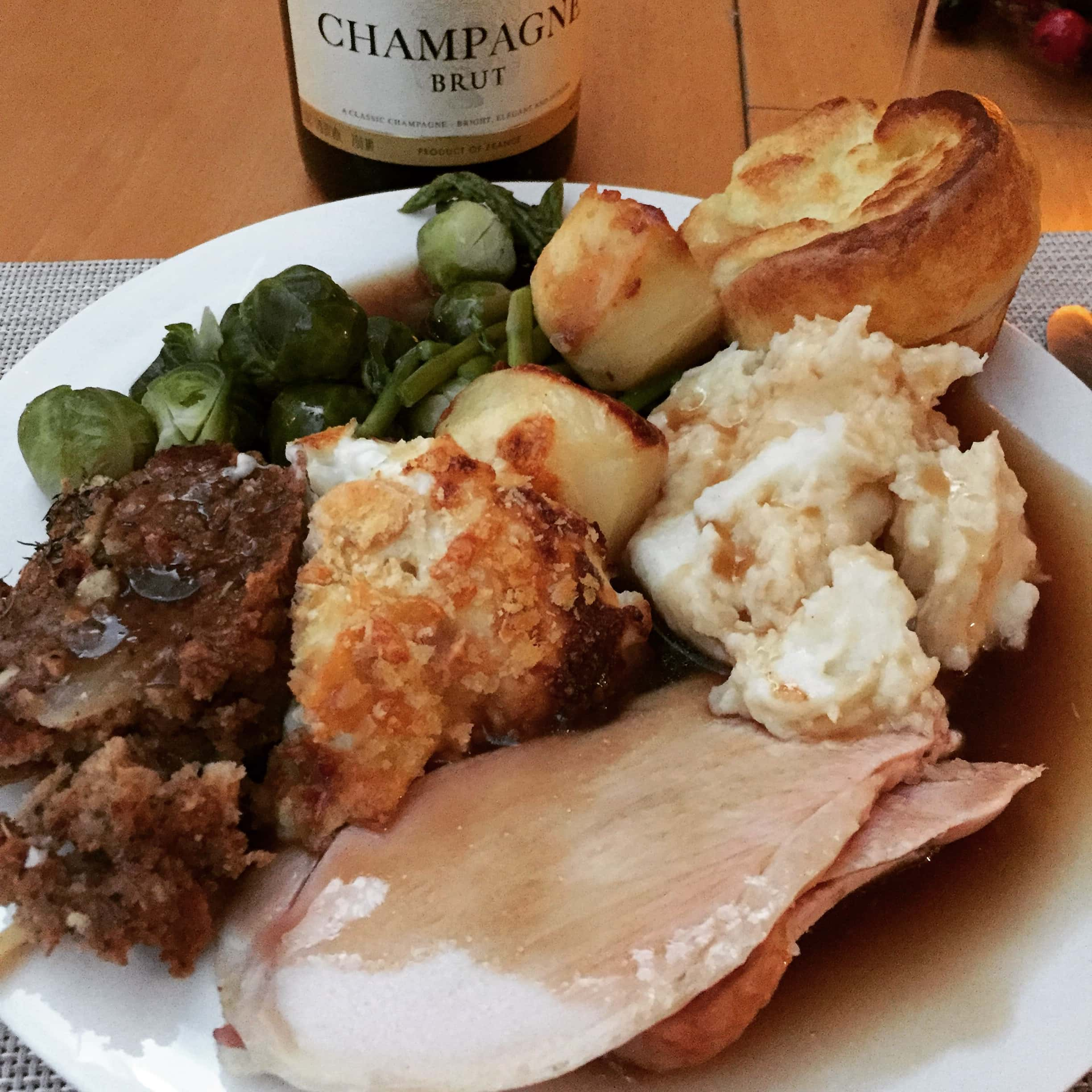 roast dinner on a plate with champagne in the background