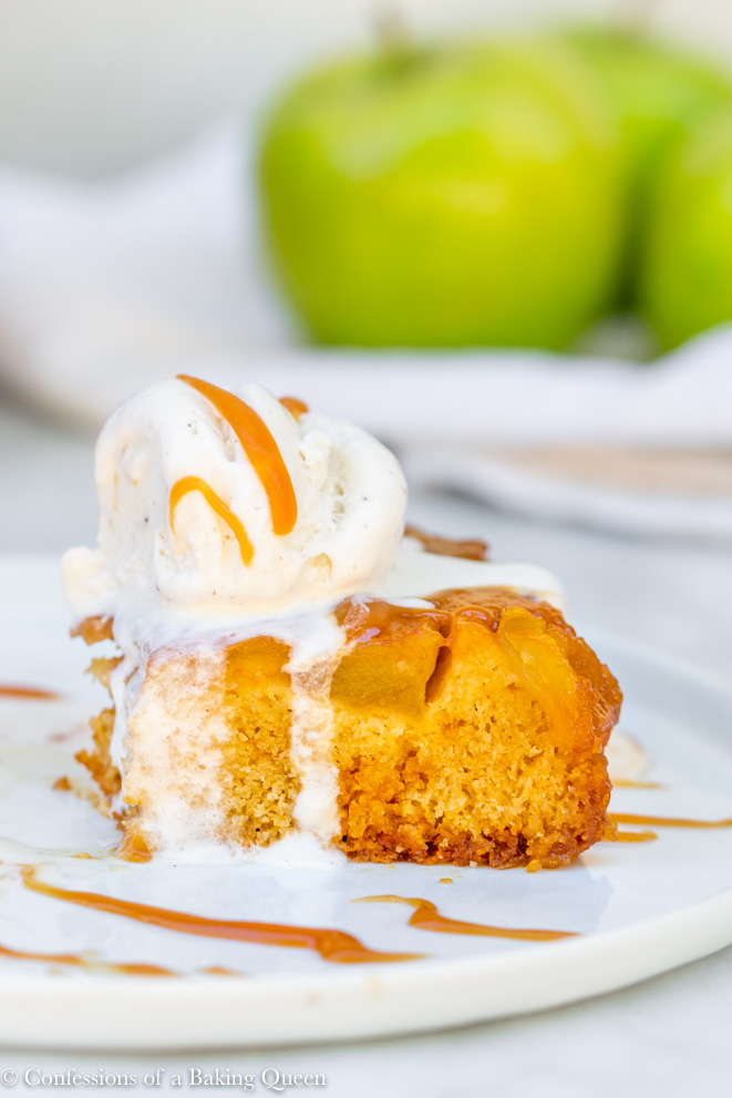 side angle of upside down salted caramel apple cake with vanilla ice cream
