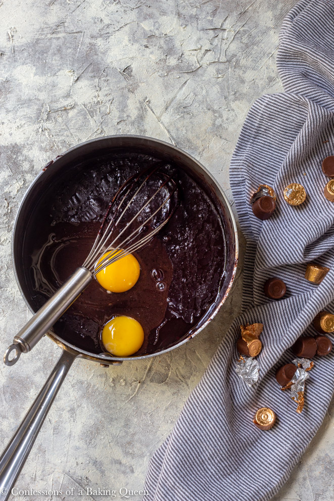 egg and egg yolk added to brownie batter in a large saucepan