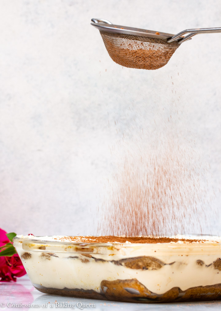 sieve shaking cocoa powder on top of tiramisu