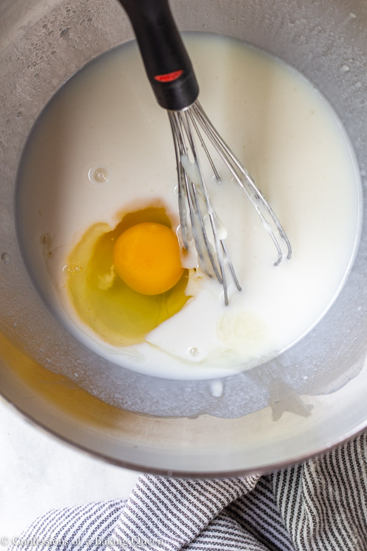 egg added to milk in a large metal bowl with a whisk